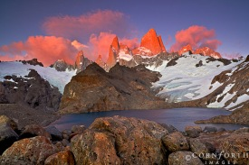 Argentina, Santa Cruz, Los Glaciares National Park, Alpenglow illuminates Mount Fitz Roy (11,073ft/3,375m), Aguja Poincenot, and Aguja Saint Exupery above Laguna de los Tres